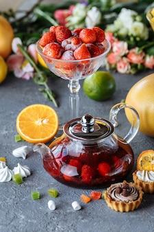 Bule de vidro com chá de frutas framboesa e hortelã em um fundo azul com frutas e decorações.