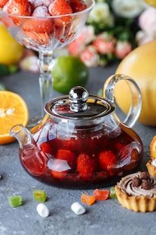 Bule de vidro com chá de frutas framboesa e hortelã sobre uma mesa azul com frutas e decorações