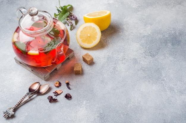 Bule de vidro com chá, hortelã e limão na mesa cinza com espaço de cópia