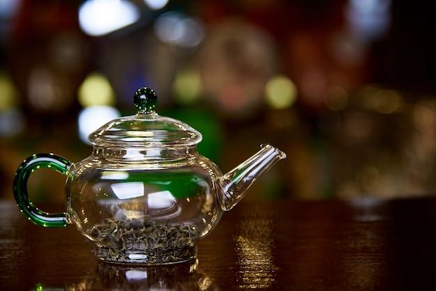 Bule de vidro com folhas de chá em um fundo escuro com bokeh.