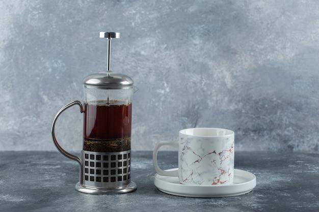 Bule de vidro com xícara na mesa cinza.