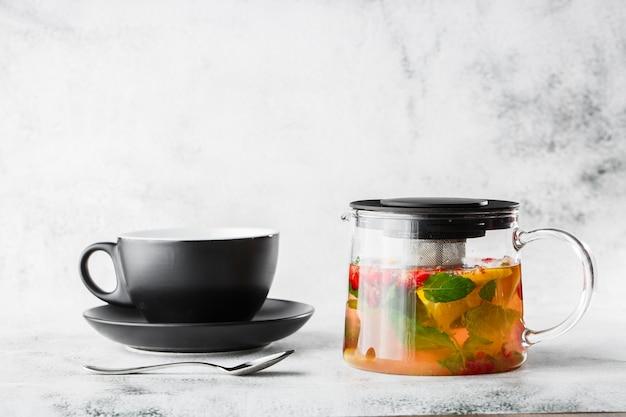 Bule de vidro de cranberry, laranja e hortelã ou chá amarelo no copo preto isolado no fundo de mármore brilhante. visão aérea, copie o espaço. publicidade para o menu de café. menu de café. foto horizontal.