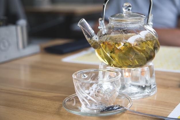 Bule de vidro e copo de vidro com chá de ervas