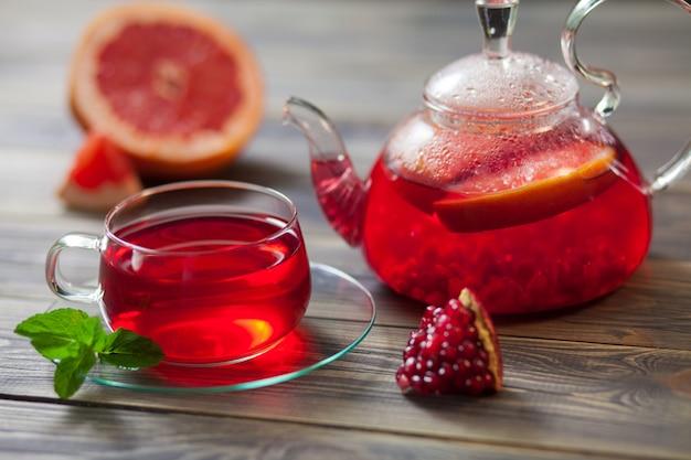 Bule de vidro e xícara de chá vermelho com uva, romã, hortelã em uma mesa de madeira marrom