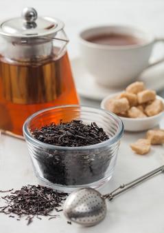 Bule de vidro transparente com chá preto orgânico solto e açúcar de cana com xícara de cerâmica branca no fundo da mesa de luz.