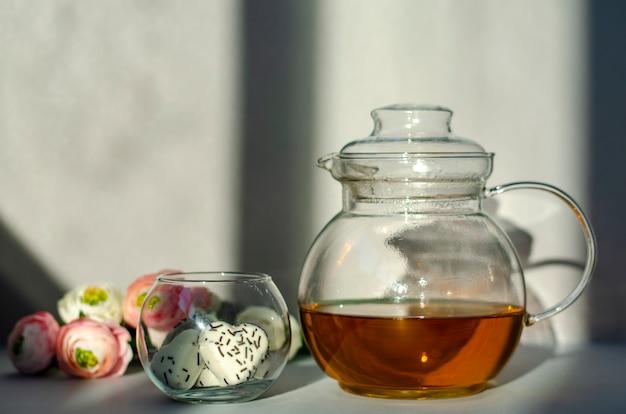 Bule de vidro transparente com chá verde, biscoitos em forma de coração e flores nos raios de luz solar de manhã.