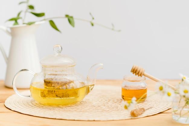 Bule de vista frontal com chá perto de pote de mel