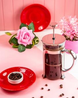 Bule de vista lateral com grãos de café e uma rosa em cima da mesa