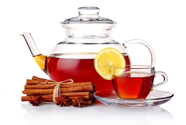 Bule e chá no copo com especiarias e limão isolado no branco