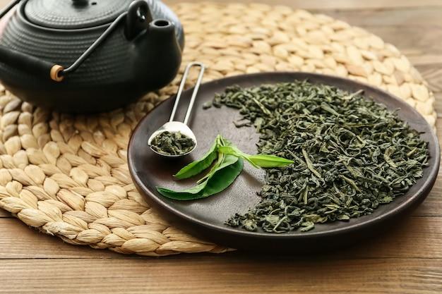 Bule e chá verde seco em prato na mesa de madeira
