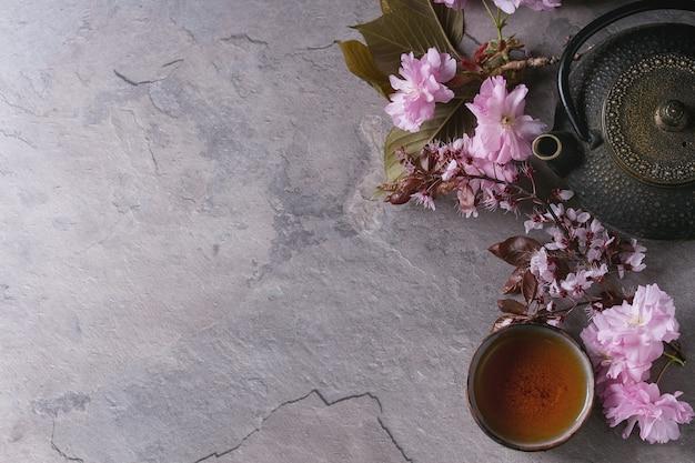 Bule e xícara de chá com ramo de flor