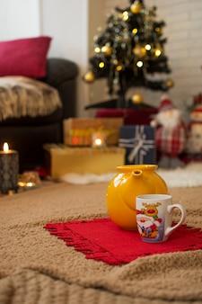 Bule e xícara de natal, no tapete da casa decorada com luzes e presentes de natal