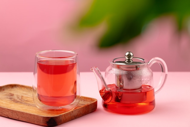 Bule e xícara de vidro com chá preto na mesa