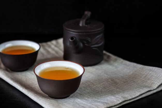 Bule e xícaras chinesas marrons em uma mesa de madeira preta