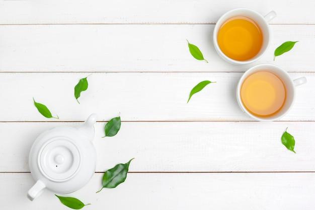 Bule e xícaras de chá em um branco de madeira