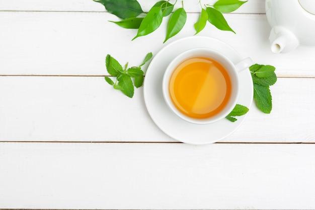 Bule e xícaras de chá em um fundo branco de madeira
