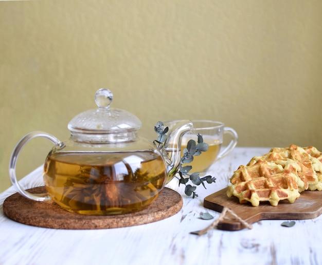 Bule transparente com chá floral, eucalipto e waffles na mesa branca e amarelo