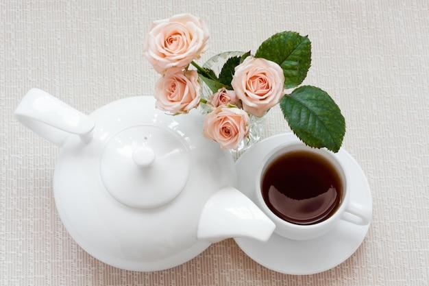 Bule, xícara e rosas em um prato