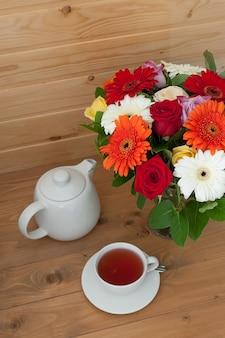 Bule, xícara e um lindo buquê de primavera em uma mesa de madeira. festa do chá.