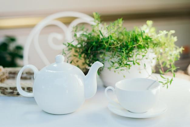 Bules de cerâmica brancos e ingredientes de chá, em cima de uma mesa branca com um vaso de flores.