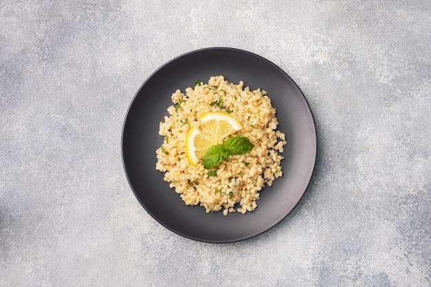 Bulgur cozido com limão fresco e hortelã em um prato. um prato oriental tradicional chamado tabouleh. vista superior do plano de fundo cinza de concreto, copie o espaço