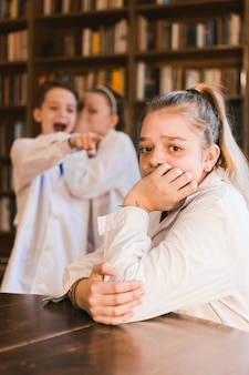Bullies fofocando e zombando jovem garota chorando