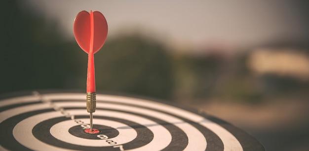 Bullseye ou dardos tem um lançamento de seta de dardo atingindo o centro de um alvo de tiro.