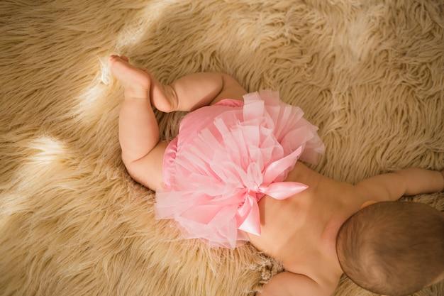 Bunda de menina em calcinha rosa com babados em cobertor bege fofo