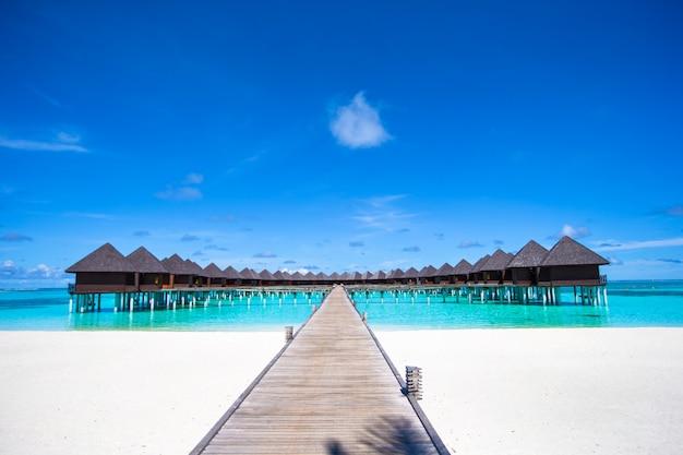 Bungalows de água e cais de madeira nas maldivas