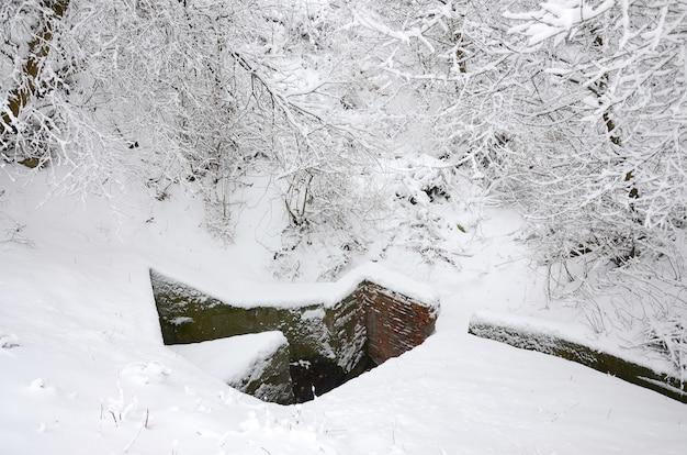 Bunker subterrâneo de antigas paredes de tijolos no inverno depois da queda de neve