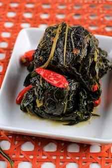 Buntil é um alimento tradicional da indonésia feito de folhas de mamão / mandioca recheadas com coco ralado, petai cina e anchova. popular na culinária javanesa e sudanesa