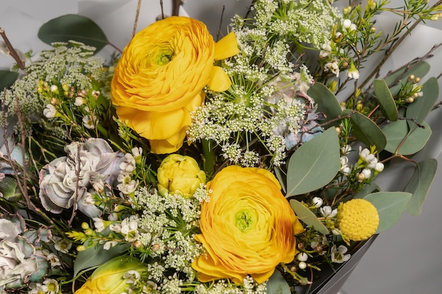 Buquê amarelo de flores amarelas e laranja em fundo cinza
