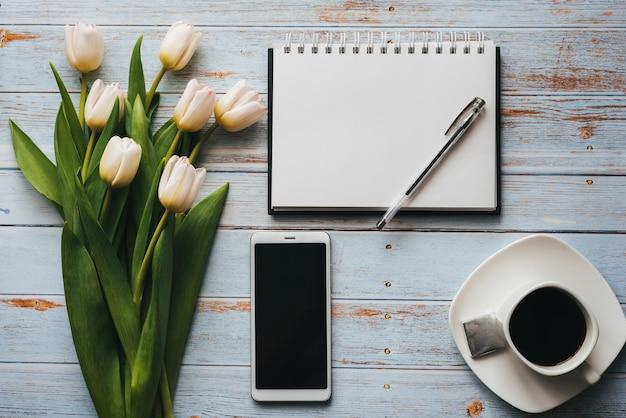 Buquê branco de tulipas com xícara de café, smartphone e caderno vazio