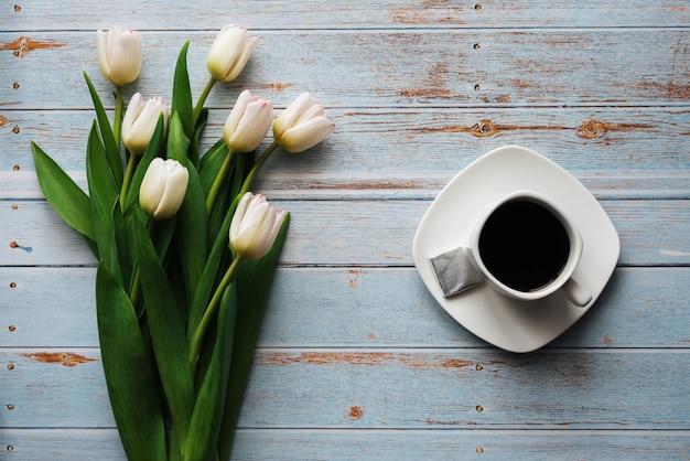 Buquê branco de tulipas em um fundo azul de madeira com uma xícara de café