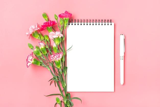 Buquê colorido de diferentes flores de cravo rosa, caderno branco, caneta em fundo rosa