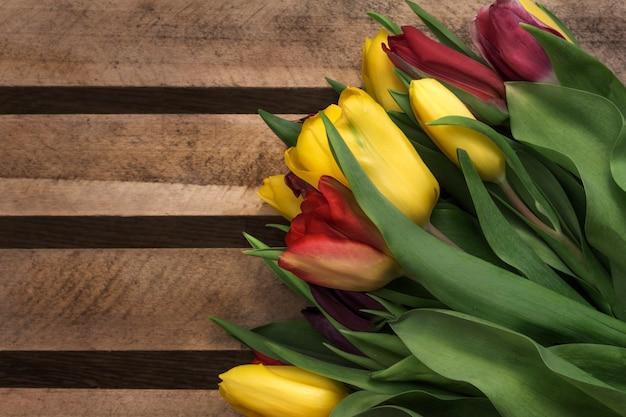 Buquê colorido de tulipas em um fundo de madeira.