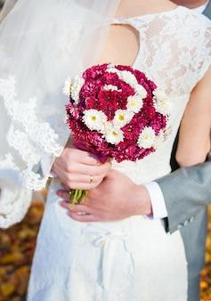 Buquê colorido sendo realizado por uma noiva e noivo