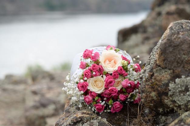 Buquê da noiva de rosas cor de rosa e branco flores encontra-se em um log pelo lago
