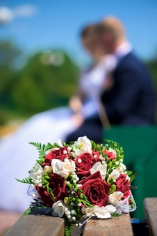 Buquê da noiva em um banco no turva casal de amantes
