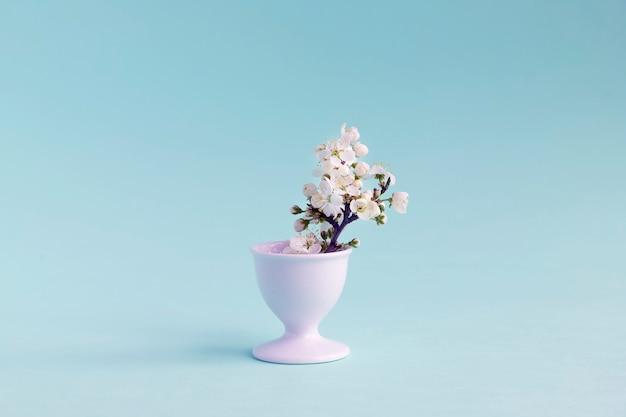 Buquê de ameixa cereja desabrochando em um pequeno vaso. fundo neutro azul. copie o espaço.