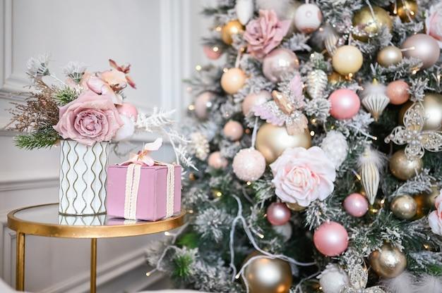 Buquê de ano novo em um vaso, uma caixa de presente delicadamente rosa na mesa de cabeceira de vidro