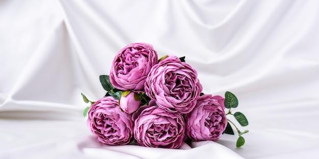 Buquê de belas peônias violetas em fundo de tecido de seda branco. copie o espaço. cartão de felicitações. flores para presente