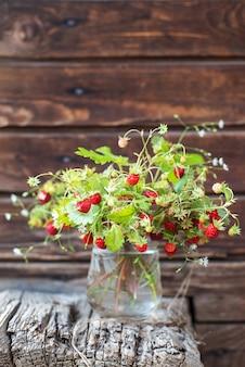 Buquê de berry em um copo em uma parede de madeira
