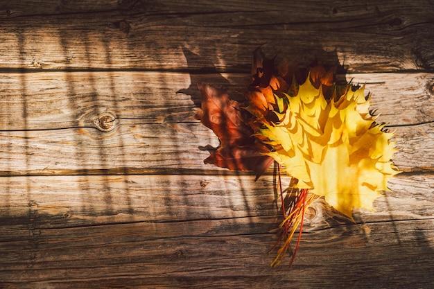 Buquê de cartão de ação de graças com folhas de bordo vermelho amarelo brilhante em um fundo de madeira