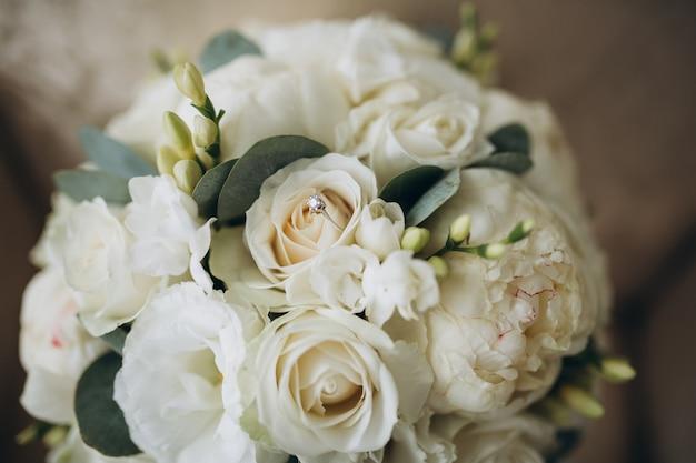 Buquê de casamento bonito e anéis de ouro
