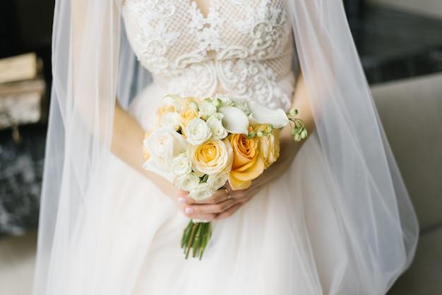 Buquê de casamento branco e laranja nas mãos da noiva