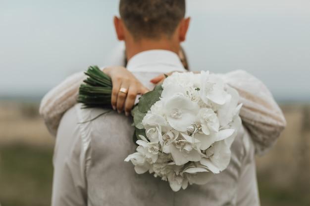 Buquê de casamento branco feito de callas e uma mulher está abraçando um homem ao ar livre