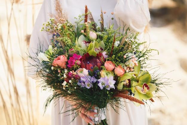 Buquê de casamento com eustoma, orquídeas, margaridas, peônias e flores silvestres no estilo boho em um fundo brilhante