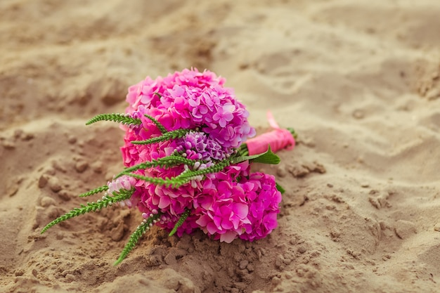 Buquê de casamento com flox rosa deitado na areia