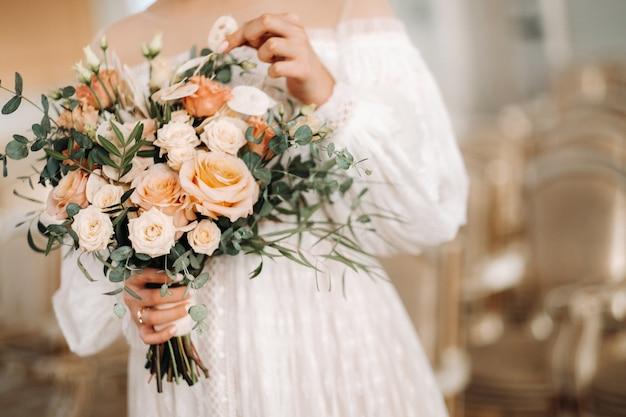 Buquê de casamento com peônias nas mãos da noiva sob o véu. manhã da noiva.